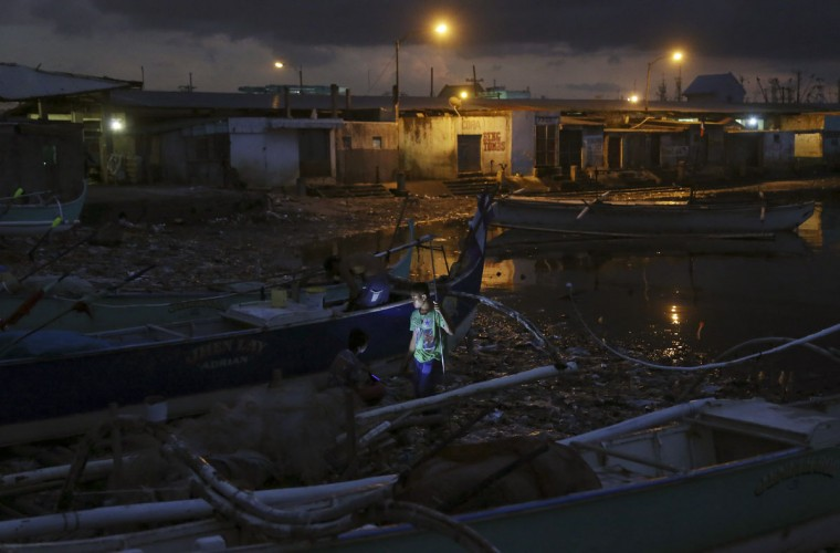 A Filipino fisherman joins others as they work on the repairs of their boat at a coastal village in Navotas, north of Manila, Philippines Monday, March 23, 2015. (AP Photo/Aaron Favila)