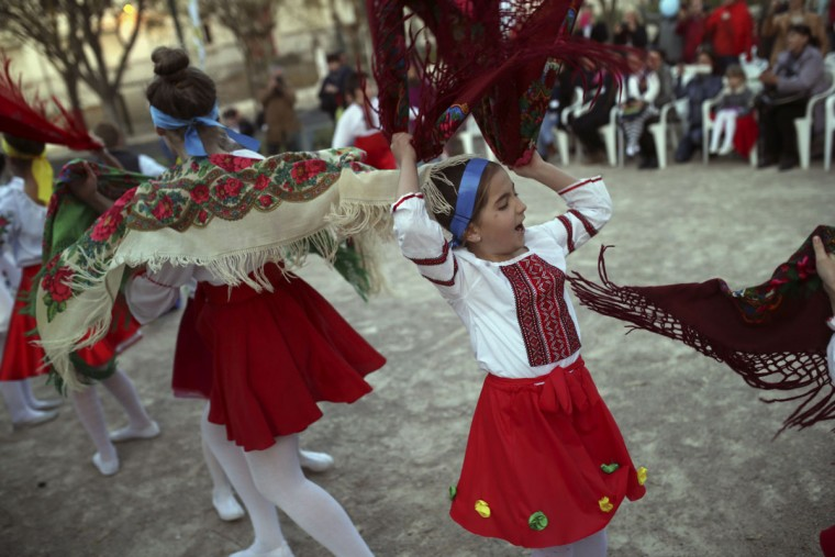 Girls wearing Ukrainian traditional costumes perform a popular dance during a cultural meeting Saturday, March 28, 2015, in Lisbon, Portugal. The event is a part of a program to promote and unite the culture of eleven different nationalities who live in a same local district. (AP Photo/Francisco Seco)