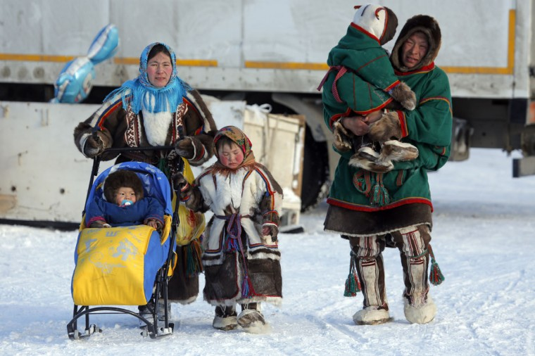 In this photo taken on Sunday, March 15, 2015, a Nenets family walks after the Reindeer Herder's Day in the city of Nadym, in Yamal-Nenets Region, 2500 kilometers (about 1553 miles) northeast of Moscow, Russia. Some participants at the Reindeer Herder's Day travel hundreds of kilometers across the frozen tundra to attend the competition in the region in northern Siberia, more than half of the territory of which lies above the Arctic Circle. (AP Photo/Dmitry Lovetsky)