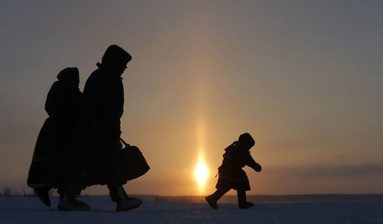 In this photo taken on Sunday, March 15, 2015, a Nenets family walks after the Reindeer Herder's Day holiday in the city of Nadym, in Yamal-Nenets Region, 2500 km (about 1553 miles) northeast of Moscow, Russia. Some participants at the Reindeer Herder's Day travel hundreds of kilometers across the frozen tundra to attend the competition in the region in northern Siberia, more than half of the territory of which lies above the Arctic Circle. (AP Photo/Dmitry Lovetsky)