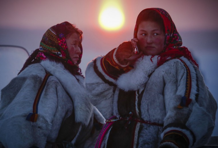 In this photo taken on Sunday, March 15, 2015, Nenets women speak at sunset after the Reindeer Herder's Day holiday in the city of Nadym, in Yamal-Nenets Region, 2500 kilometers (about 1553 miles) northeast of Moscow, Russia. For the indigenous nomadic Nenets people, the Reindeer Herderís Day offers a chance to show their prowess in wrestling, high jumps and other traditional local sports, but, above all, reindeer races. (AP Photo/Dmitry Lovetsky)