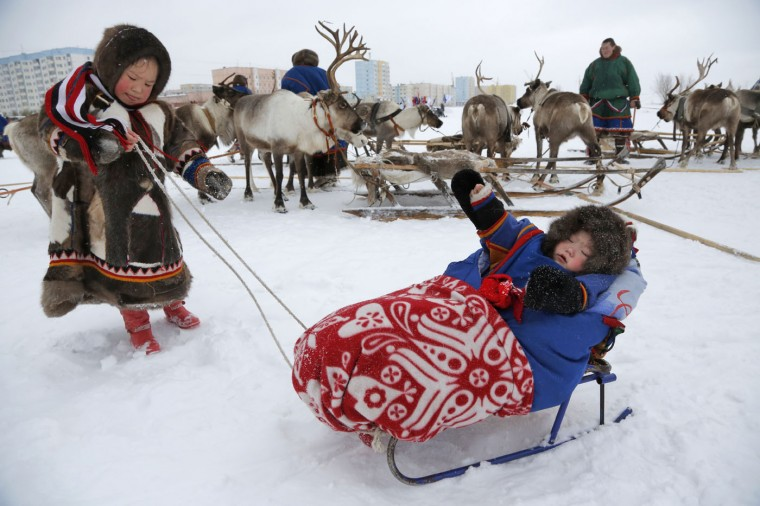 In this photo taken on Sunday, March 15, 2015, Nenets children attend the Reindeer Herder's Day holiday in the city of Nadym, in Yamal-Nenets Region, 2500 kilometers (about 1553 miles) northeast of Moscow, Russia. For the indigenous nomadic Nenets people, the Reindeer Herderís Day offers a chance to show their prowess in wrestling, high jumps and other traditional local sports, but, above all, reindeer races. (AP Photo/Dmitry Lovetsky)