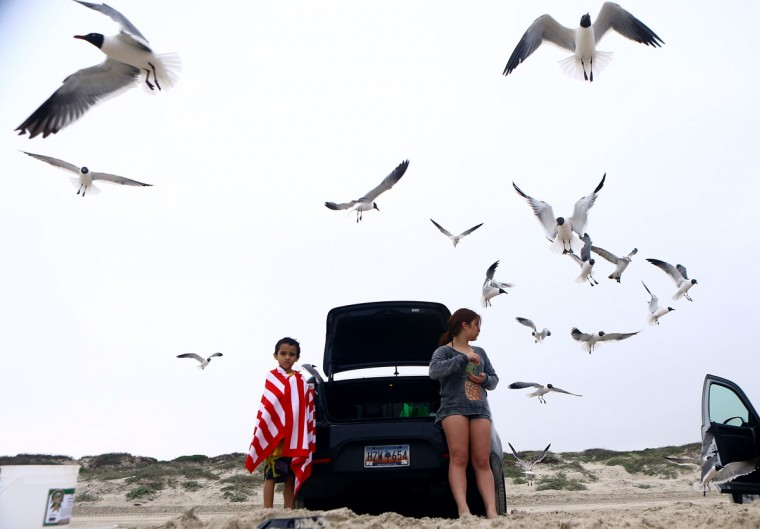 Jon Marquez, 9, right, and McCoy Gonzales eat snacks as sea gulls fly near by during spring break Tuesday, March 17, 2015, at JP Luby Surf Park in Corpus Christi, Texas. (AP Photo/Corpus Christi Caller-Times, Gabe Hernandez)