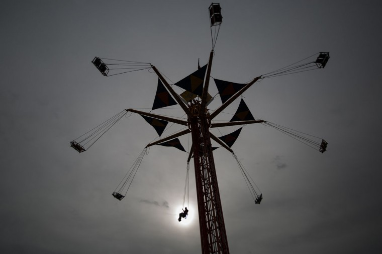 Two carnival goers take evening ride on the YoYo swing during the Wright's Amusements Carnival at the Ector County Coliseum, Monday, March 30, 2015. (AP Photo/Odessa American, Courtney Sacco)
