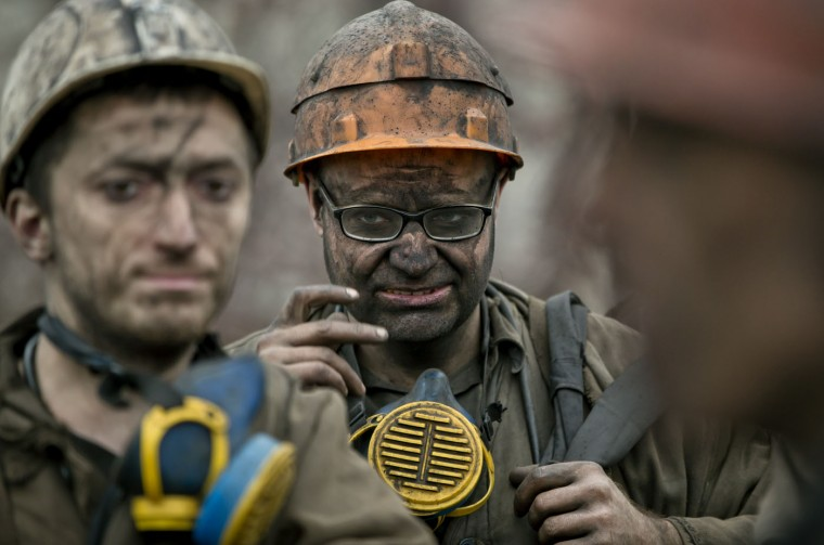 Ukrainian coal miners wait for a bus after exiting the underground of the Zasyadko mine in Donetsk, Ukraine, Wednesday, March 4, 2015. (AP Photo/Vadim Ghirda)