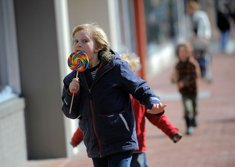 Asher Cleverley, 8, runs down Caroline Street in downtown Fredericksburg, Va with his brothers and mother while enjoying a lollipop and a day off of school due to icy conditions, Monday, March 2, 2015. Temperatures reached in the high 40s on Monday afternoon after a weekend of ice and cold temperatures. (AP Photo/The Free Lance-Star, Suzanne Carr Rossi)