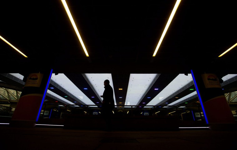 A man is silhouetted as he walks past the Robson Square ice rink in downtown Vancouver, British Columbia, Thursday, March 19, 2015. (AP Photo/The Canadian Press, Darryl Dyck)