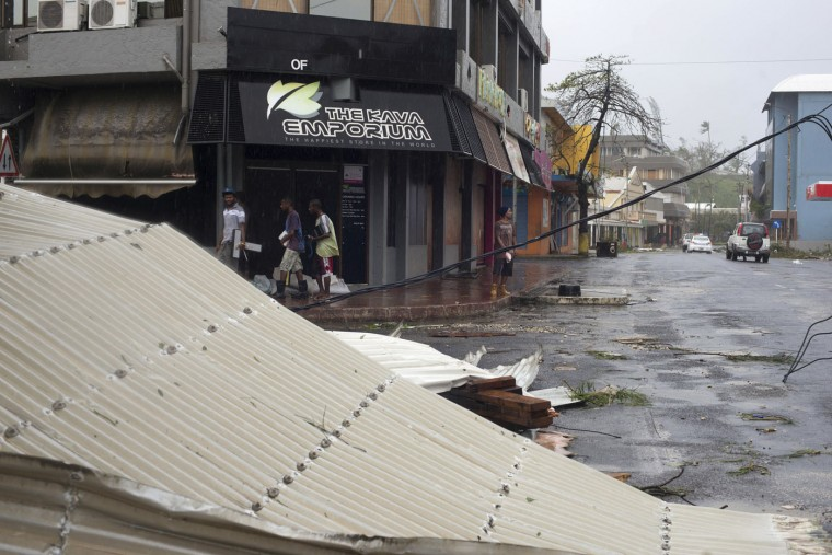 In this image provided by UNICEF Pacific, people walk past debris is scattered on a street in Port Vila, Vanuatu, Saturday, March 14, 2015, in the aftermath of Cyclone Pam. Winds from the extremely powerful cyclone that blew through the Pacific's Vanuatu archipelago are beginning to subside, revealing widespread destruction. (AP Photo/UNICEF Pacific, Humans of Vanuatu)