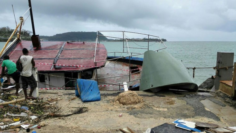 In this photo provided by China's Xinhua News Agency, locals stand by a tilted boat in Port Vila, Vanuatu, after Cyclone Pam ripped through the tiny South Pacific archipelago, Sunday, March 15, 2015. Packing winds of 270 kilometers (168 miles) per hour, Cyclone Pam tore through Vanuatu early Saturday, leaving a trail of destruction. (AP Photo/Xinhua, Luo Xiangfeng)
