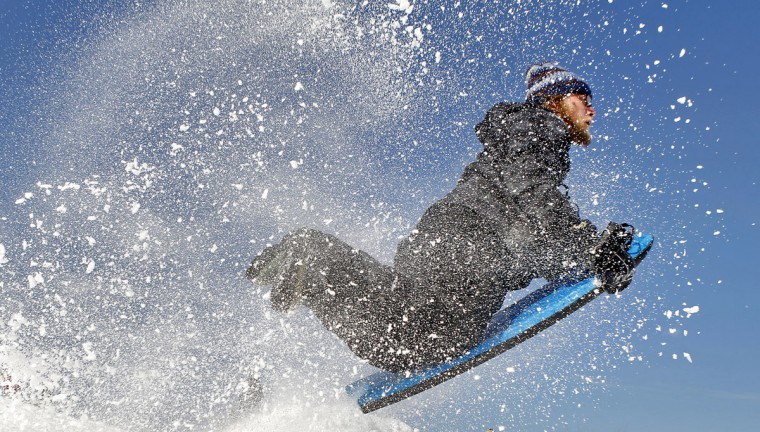 Joseph Smith flies through the air after hitting a snow pile while sledding Tuesday, Feb. 17, 2015 afternoon at Riverview Farm Park in Newport News, Va. (AP Photo/The Daily Press, Jonathon Gruenke)