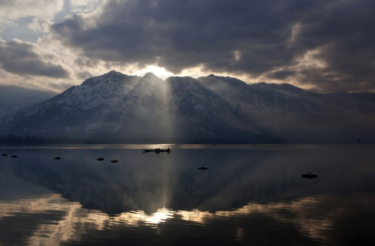 The sun peeks through a gap between clouds and a mountain as Kashmiri fishermen row their boats on their way home after working in Dal Lake in Srinagar, in Indian-controlled Kashmir, on Tuesday, March 10, 2015. Dal Lake, famous for its natural beauty and a popular destination for international and domestic tourists, has shrunk in the past two decades. According to local reports, it has decreased by more than half to 11 square kilometers (4.2 square miles) and lost 12 meters (36 feet) in depth. (AP Photo/Dar Yasin)