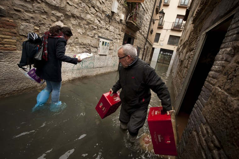 Gregorio Fernandez, 73, walks with plastic boxes on a flooded old street in Tudela, northern Spain, on Friday, Feb. 27, 2015 after a few days of heavy rain. (AP Photo/Alvaro Barrientos)