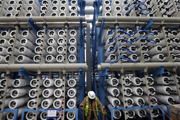 A worker climbs stairs among some of the 2,000 pressure vessels that will be used to convert seawater into fresh water through reverse osmosis in the western hemisphere's largest desalination plant in Carlsbad, Calif., on Wednesday, March 11, 2015. As California endures the worst drought in its recorded history, some are turning to the sea for relief. The Carlsbad Desalination Project, scheduled to start operations in late 2015, is expected to provide 50 million gallons of fresh drinking water a day. (AP Photo/Gregory Bull)