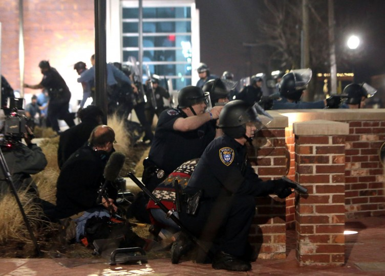 Police take cover after two officers were shot while standing guard in front of the Ferguson Police Station on Thursday, March 12, 2015 in Ferguson, Mo. (Laurie Skrivan/St. Louis Post-Dispatch/TNS)