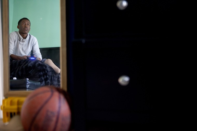 Hammond High School junior basketball player Essien Ture, 16, is reflected in a mirror resting his leg and playing a video game (NBA 2K15) in his room. (Jen Rynda/BSMG)