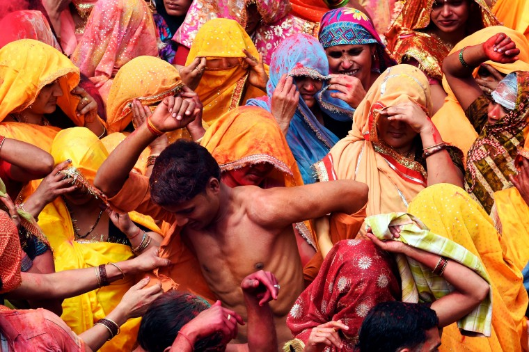 An Indian man is stripped of his shirt as he is surrounded by women at the beginning of the Dadjee ka Huranga festivities in the north Indian town of Baldeo. 'Huranga' is a game played between men and women a day after Holi, the festival of colors, during which men drench women with liquid colors and women tear off the clothes of the men. (Roberto Schmidt/AFP-Getty Images)
