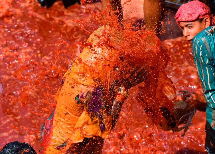 An Indian woman gets drenched by a bucket of colored water during the Dadjee ka Huranga festivities in the north Indian town of Baldeo 'Huranga' is a game played between men and women a day after Holi, the festival of colors, during which men drench women with liquid colors and women tear off the clothes of the men. (Roberto Schmidt/AFP-Getty Images)