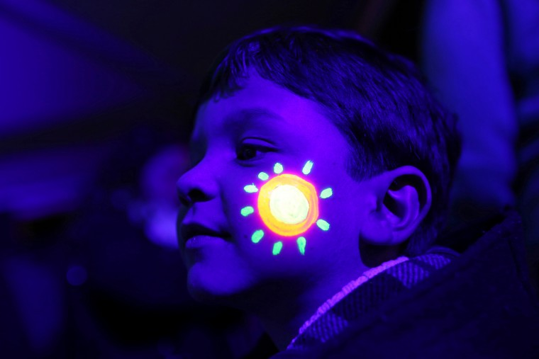 A boy with his face decorated with luminous ink poses for a photograph with others during the symbolic switching off of the lights known as Earth Hour in Lisbon, Portugal. At 8:30 p.m. local time, individuals, businesses, cities and landmarks around the world switched off their lights for one hour to focus attention on climate change. (Francisco Seco/Associated Press)