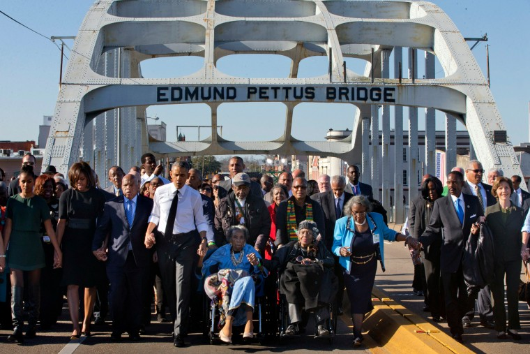 """President Barack Obama, fourth from left, walks holding hands with Amelia Boynton, who was beaten during """"Bloody Sunday,"""" as they and the first family and others including Rep. John Lewis, D-Ga, left of Obama, walk across the Edmund Pettus Bridge in Selma, Ala. for the 50th anniversary of the landmark event of the civil rights movement. At far left is Sasha Obama and at far right is former first lady Laura Bush. (Jacquelyn Martin/Associated Press)"""
