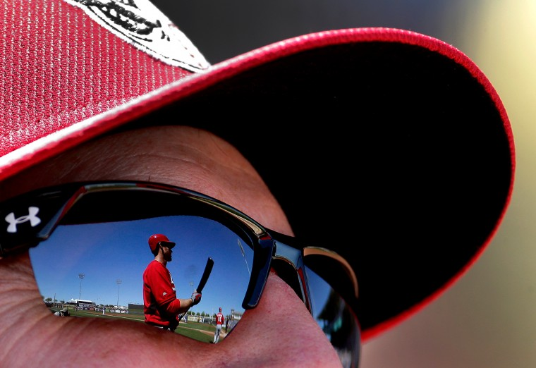 Cincinnati Reds' Brennan Boesch is reflected in manager Bryan Price's sunglasses as he warms up on deck during the second inning of a spring training baseball game against the Kansas City Royals in Surprise, Ariz. (Charlie Riedel/Associated Press)