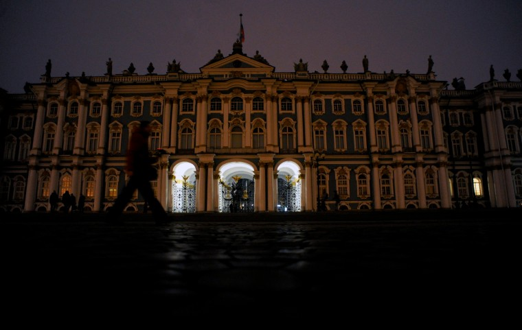 People walk past the State Hermitage Museum with its lights off as part of the Earth Hour environmental campaign in central Saint Petersburg. (Olga Maltseva/AFP-Getty Images)