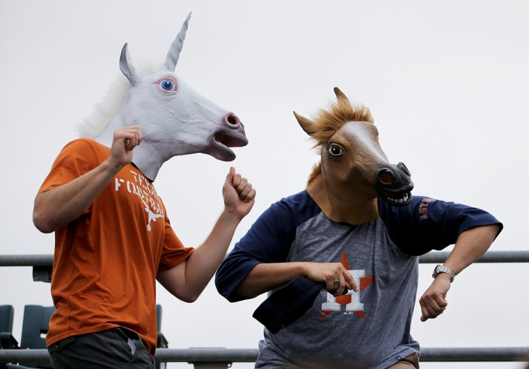 Houston Astros fans Tony Sullivan, left, and Omar Enriquez, both of Houston, Texas, dance while wearing masks during the eighth inning of an exhibition spring training baseball game between the Astros and the New York Yankees in Kissimmee, Fla. (David Goldman/Associated Press)