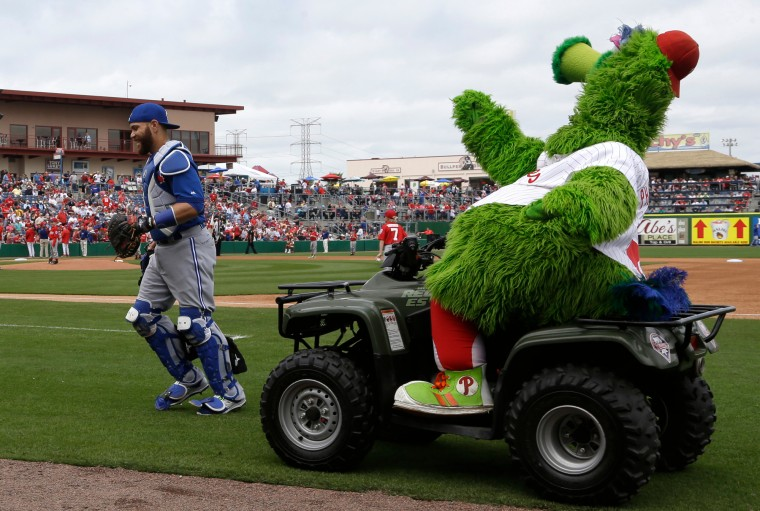 The Philadelphia Phillies Phanatic mascot rides on a cart past Toronto Blue Jays catcher Russell Martin during a spring training baseball exhibition game, Saturday, March 7, 2015, in Clearwater, Fla. (Lynne Sladky/Associated Press)