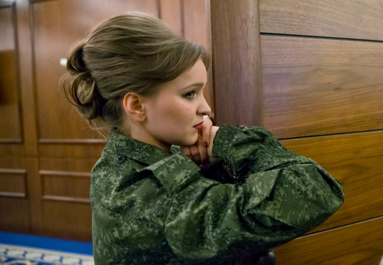 A Russia-backed female rebel fighter watches as colleagues perform during a beauty contest involving women from the main separatist battalions in Donetsk, Ukraine. Self-proclaimed authorities in the rebel-held Donetsk held a beauty pageant for female rebel fighters on the eve of March 8, a women's day widely celebrated throughout the former Soviet Union. (Vadim Ghirda/Associated Press)