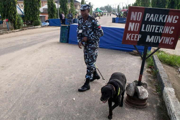 A police officer uses a dog to sweep the area before the arrival of incumbent Nigerian president to cast his ballot during presidential elections at polling station in Otuoke. Voting began in Nigeria's general election but delays were reported countrywide because of technical problems in accrediting electors. (Florian Plaucheur/AFP-Getty Images)