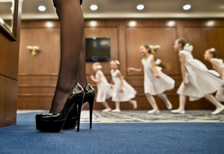 A woman checks herself in a mirror as child ballerinas warm up before their performance during a beauty contest involving women from the main separatist battalions in Donetsk, Ukraine. Self-proclaimed authorities in the rebel-held Donetsk held a beauty pageant for female rebel fighters on the eve of March 8, a women's day widely celebrated throughout the former Soviet Union. (Vadim Ghirda/Associated Press)