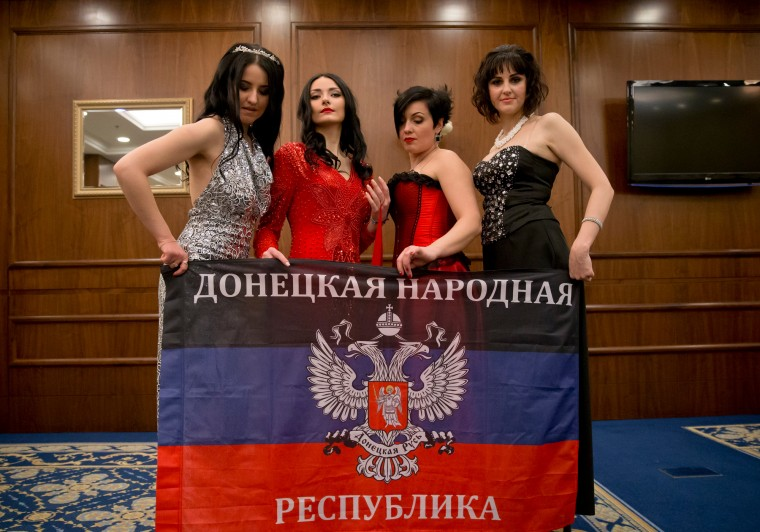 Russia-backed female rebel fighters pose with the flag of the Donetsk People's Republic during a beauty contest involving women from the main separatist battalions in Donetsk, Ukraine. Self-proclaimed authorities in the rebel-held Donetsk held a beauty pageant for female rebel fighters on the eve of March 8, a women's day widely celebrated throughout the former Soviet Union. (Vadim Ghirda/Associated Press)