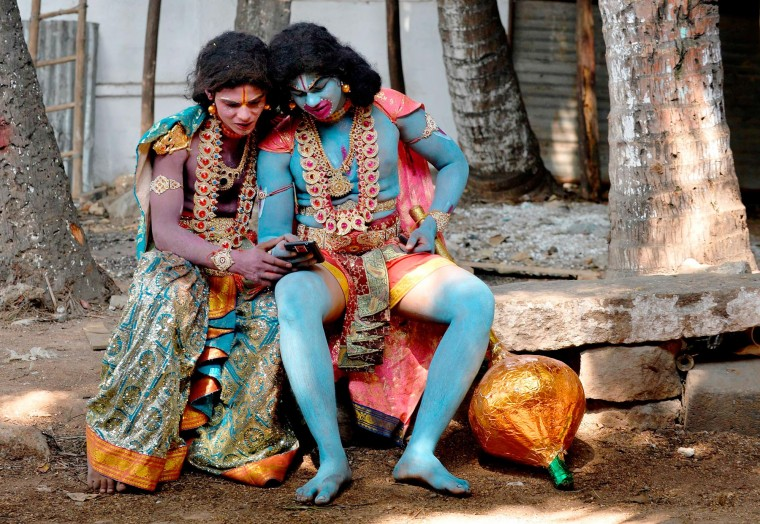 Indian artists dressed as Hindu monkey god Hanuman (R) and Lakshman watch a video on their mobile phone during Rama Navami festival celebrations at a temple in Bangalore. Rama Navami is a Hindu festival, celebrating the birth of the god Rama whom Hindus consider is the seventh incarnation of Lord Vishnu and is the oldest known Hindu god having human form. (Manjunath Kiran/AFP-Getty Images)