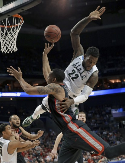 Georgia's Marcus Thornton, front, is fouled by Michigan State's Branden Dawson, back, during the first half of an NCAA tournament college basketball game in the Round of 64 in Charlotte, N.C., Friday, March 20, 2015. (AP Photo/Gerald Herbert)