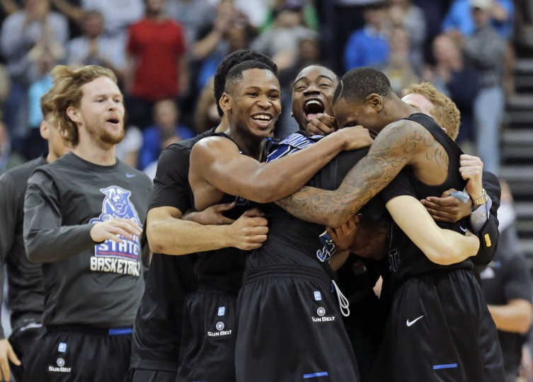 Georgia State players celebrate as they surround R.J. Hunter, center, after he made the game winning shot against Baylor an NCAA tournament second round college basketball game, Thursday, March 19, 2015, in Jacksonville, Fla. Georgia State won 57-56. (AP Photo/Chris O'Meara)