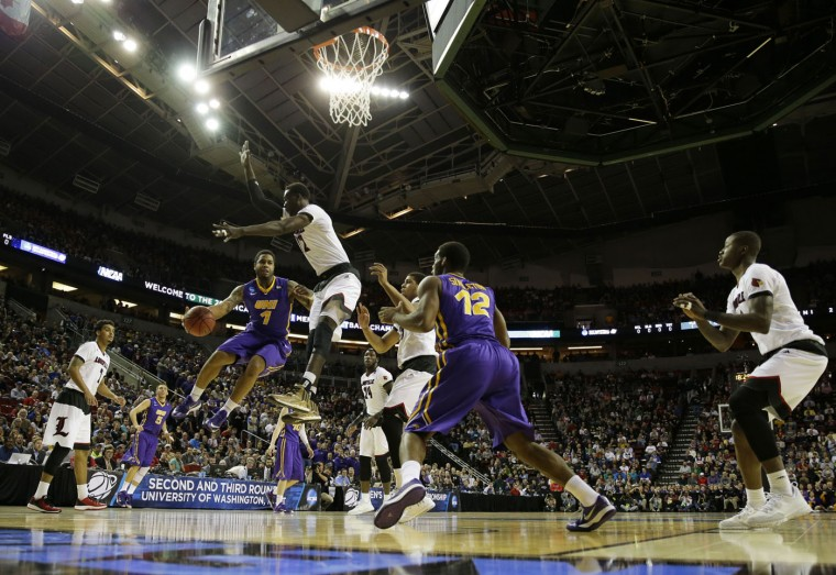 Northern Iowa's Deon Mitchell (1) passes around Louisville's Mangok Mathiang to Northern Iowa's Marvin Singleton (12) during the first half of an NCAA college basketball tournament game in the Round of 32, Sunday, March 22, 2015, in Seattle. (AP Photo/Ted S. Warren)