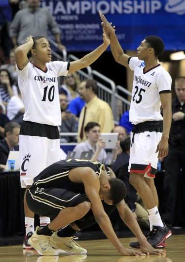 Cincinnati guard Troy Caupain, left, congratulates teammate Kevin Johnson after Purdue forward Vince Edwards, bottom, missed a last-second shot during overtime of an NCAA tournament second round college basketball game in Louisville, Ky., Thursday, March 19, 2015. Cincinnati won 66-65. (AP Photo/David Stephenson)