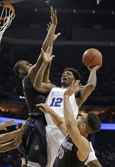 Duke's Justise Winslow, center, shoots between San Diego State's Skylar Spencer, left, and J.J. O'Brien, right, during the first half of an NCAA tournament college basketball game in the Round of 32 in Charlotte, N.C., Sunday, March 22, 2015. (AP Photo/Gerald Herbert)