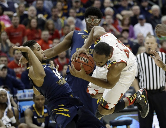 Maryland's Dez Wells, right, collides with West Virginia's Gary Browne, left, and Devin Williams futinh the first half of an NCAA tournament college basketball game in the Round of 32 in Columbus, Ohio, Sunday, March 22, 2015. (AP Photo/Tony Dejak)