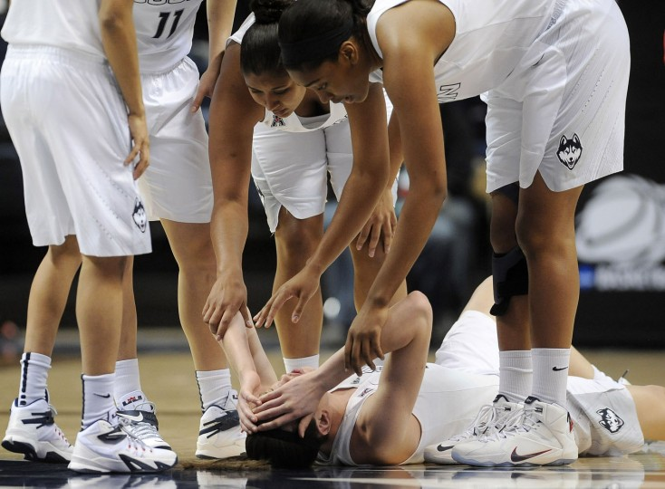 Connecticutís Kaleena Mosqueda-Lewis, top center, with Morgan Tuck, top right, reach down to check on teammate Breanna Stewart, bottom, after Stewart collided with another player during the first half of a women's college basketball game against Rutgers in the second round of the NCAA tournament, Monday, March 23, 2015, in Storrs, Conn. (AP Photo/Jessica Hill)