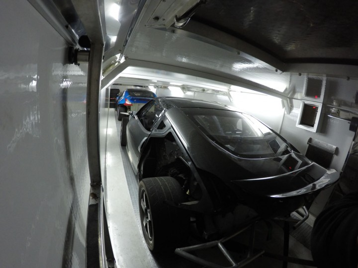 """Sorry for the jump in time, but it takes all hands to push these cars out of the shop and onto the liftgate and into the trailer. But as you can see, both race cars fit up top on the second floor above the work space below. For the sake of keeping our new body panels """"new"""" for the first round, we leave most of them off for testing."""