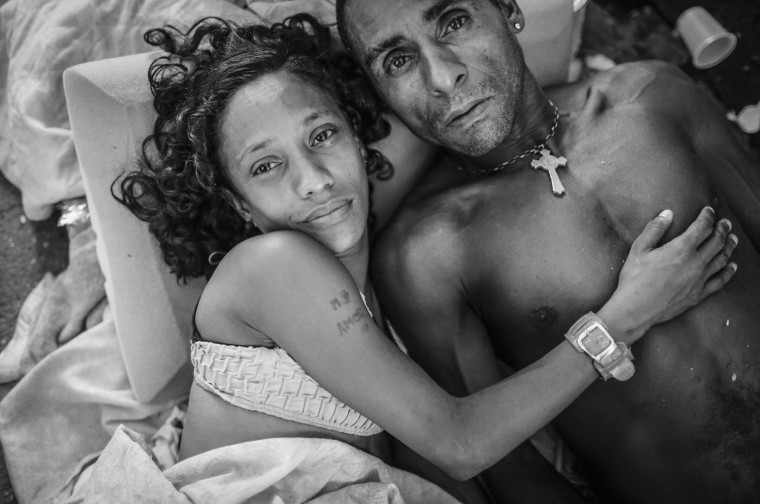 Couple Eduardo and Michelle pose while lying together on the sidewalk in the Centro neighborhood on March 23, 2015 in Rio de Janeiro, Brazil. Michelle said she has lived in the streets since she was 7 years old.
