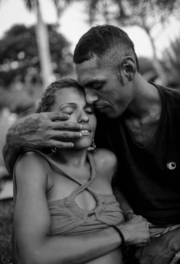 Vanessa Priscilla is kissed by Thompson while posing in a park where homeless live in the West Zone on March 27, 2015 in Rio de Janeiro, Brazil. They both live in the park.