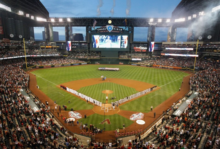 The San Francisco Giants and the Arizona Diamondbacks stand for the national anthem before the Opening Day MLB game at Chase Field on April 6, 2015 in Phoenix, Arizona. (Photo by Christian Petersen/Getty Images)