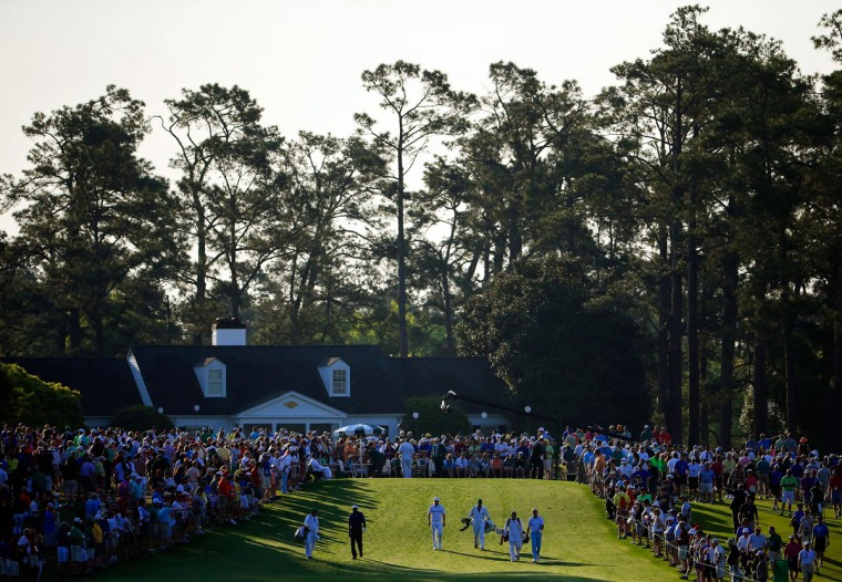 A group of players and caddies walk off the first tee during the first round of the 2015 Masters Tournament at Augusta National Golf Club on April 9, 2015 in Augusta, Georgia. (Photo by Jamie Squire/Getty Images)