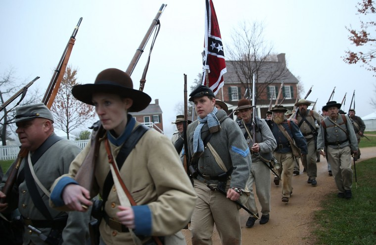 American Civil War re-enactors dressed as members of the North Carolina 26th Infantry march during a re-enactment of the Battle of Appomattox Court House at the Appomattox Court House National Historical Park April 8, 2015 in Appomattox, Virginia. Today is the 150th anniversary of Confederate General Robert E. Lee's surrender of the Army of Northern Virginia to Union forces commanded by General Ulysses S. Grant in the McLean House at Appomattox, Virginia. The surrender marked the beginning of the end of the American Civil War in 1865. (Photo by Win McNamee/Getty Images)