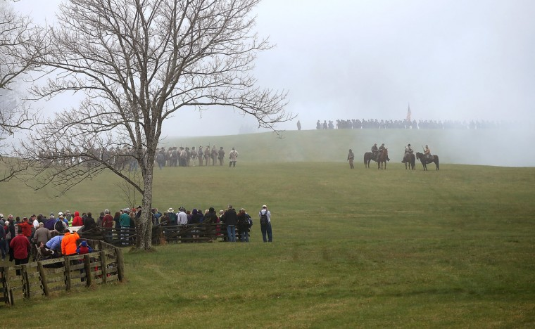 Spectators watch as American Civil War re-enactors dressed as Union and Confederate forces take part in a re-enactment of the Battle of Appomattox Court House at the Appomattox Court House National Historical Park April 8, 2015 in Appomattox, Virginia. Today is the 150th anniversary of Confederate General Robert E. Lee's surrender of the Army of Northern Virginia to Union forces commanded by General Ulysses S. Grant in the McLean House at Appomattox, Virginia. The surrender marked the beginning of the end of the American Civil War in 1865. (Photo by Win McNamee/Getty Images)
