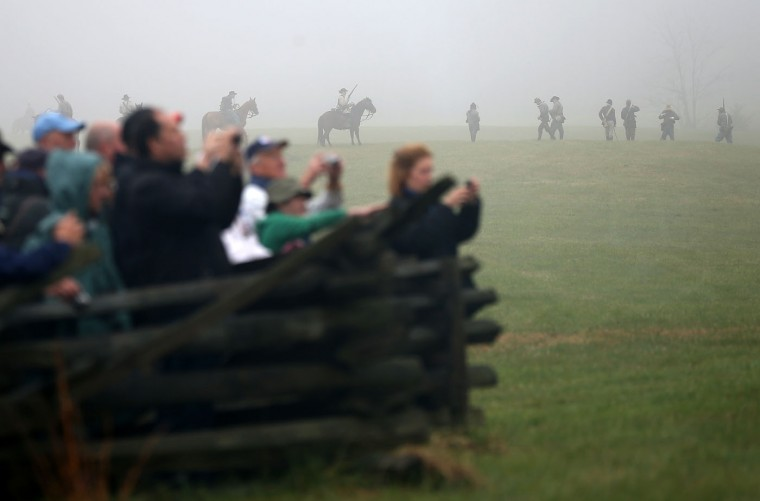 Spectators watch as American Civil War re-enactors dressed as Union cavalry take part in a re-enactment of the Battle of Appomattox Court House at the Appomattox Court House National Historical Park April 9, 2015 in Appomattox, Virginia. Today is the 150th anniversary of Confederate General Robert E. Lee's surrender of the Army of Northern Virginia to Union forces commanded by General Ulysses S. Grant in the McLean House at Appomattox, Virginia. The surrender marked the beginning of the end of the American Civil War in 1865. (Photo by Win McNamee/Getty Images)
