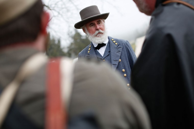 American Civil War re-enactor Thomas Lee Jessee, portraying Gen. Robert E. Lee, greets re-enactoes portraying members of the North Carolina 26th Infantry following a re-enactment of the Battle of Appomattox Court House at the Appomattox Court House National Historical Park April 9, 2015 in Appomattox, Virginia. Today is the 150th anniversary of Confederate General Robert E. Lee's surrender of the Army of Northern Virginia to Union forces commanded by General Ulysses S. Grant in the McLean House at Appomattox, Virginia. The surrender marked the beginning of the end of the American Civil War in 1865. (Photo by Win McNamee/Getty Images)