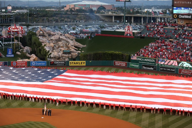 A color guard and a giant American flag are on the field during the national anthem before the Kansas City Royals and the Los Angeles Angels of Anaheim play in the Angels' home opener on April 10, 2015 in Anaheim, California. (Photo by Stephen Dunn/Getty Images)