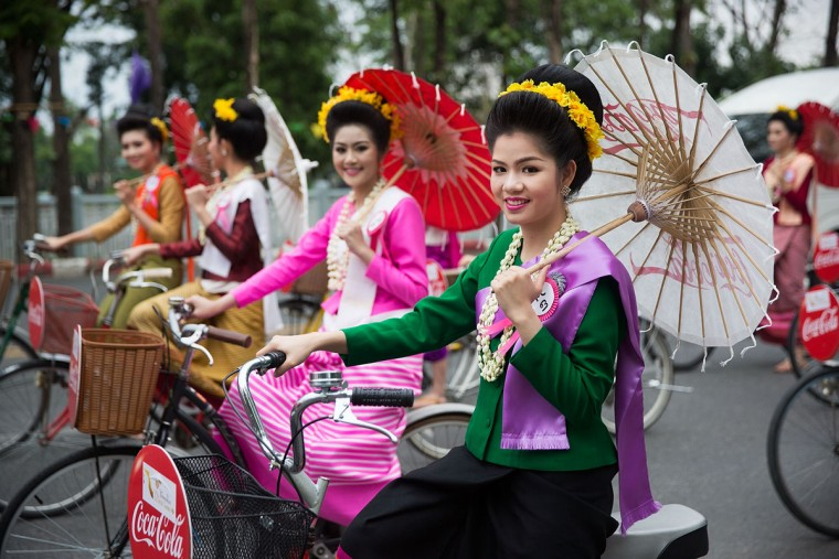 Thai beauty contestants ride bicycles down the street during a Songkran parade on April 13, 2015 in Chiang Mai, Thailand. The Songkran festival, marking the traditional Thai New Year, is celebrated each year from April 13 to 15. The throwing of water was traditionally a sign of respect and well wishing during the festival. (Photo by Taylor Weidman/Getty Images)